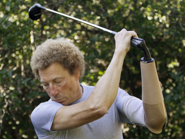 Bob Radocy of TRS Inc. swings a golf club with a golf hand replacement at his home in Boulder, Colorado August 20, 2009. Radocy designs and builds prosthetic attachments that allow amputee athletes to participate in multiple sports. The golf hand stores energy on the backswing improving power through the downstroke. (Photo by Rick Wilking/Reuters)
