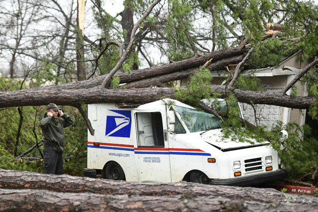 A man talks on the phone next to a damaged postal truck at an apartment complex where a reported tornado passed through Thursday, February 6, 2020, in Spartanburg, S.C. A powerful winter storm brought severe weather across the Deep South early Thursday, with high winds causing damage that killed one person, injured several others and littered at least four states. (Photo by Sean Rayford/AP Photo)