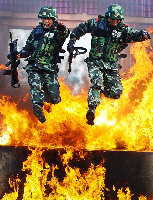 Chinese paramilitary policemen jump through a wall of fire during a training exercise at a military base in Chuzhou, China on July 25, 2012. (Photo by Associated Press)