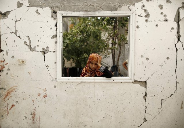 A relative reacts at a badly damaged house, which witnesses said was hit by an Israeli air strike that killed three Palestinians from the Wahdan family, as bloodstains are seen on a damaged wall in Jabaliya refugee camp in the northern Gaza Strip August 3, 2014. (Photo by Suhaib Salem/Reuters)