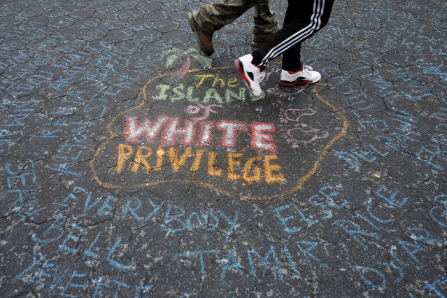 People walk over the names of people killed by police as they take part in a protest against the killing of Alton Sterling, Philando Castile and in support of Black Lives Matter during a march along Manhattan's streets in New York July 8, 2016. (Photo by Eduardo Munoz/Reuters)
