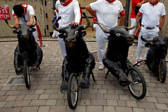 Handlers stand by their toy bulls as they prepare for another run during the Encierro Txiki (Little Bull Run) at the San Fermin festival in Pamplona, Spain July 13, 2016. (Photo by Susana Vera/Reuters)
