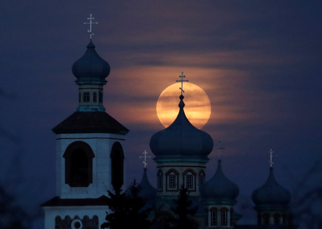 Full moon rises behind an Orthodox Church in the village of Turets, on Belarus February 9, 2020. (Photo by Vasily Fedosenko/Reuters)