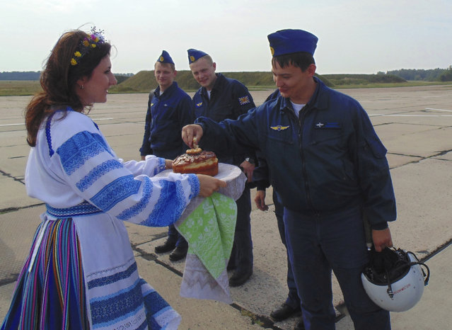 In this photo taken on Tuesday, September 12, 2017, Russian military pilots are presented with traditional welcoming bread-and-salt as they arrive at an airbase at undisclosed location in Belarus. Russia and Belarus are holding a massive war games, Zapad 2017, that due to start on Thursday near the borders of Poland, Estonia, Latvia and Lithuania. (Photo by Vayar Military Agency photo via AP Photo)