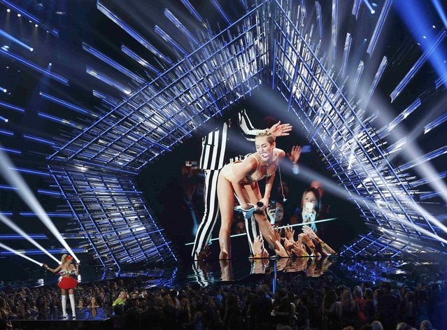Show host Miley Cyrus (L) speaks on stage as an image of her from a previous VMA Awards is shown on a large screen at the 2015 MTV Video Music Awards in Los Angeles, California August 30, 2015. (Photo by Mario Anzuoni/Reuters)