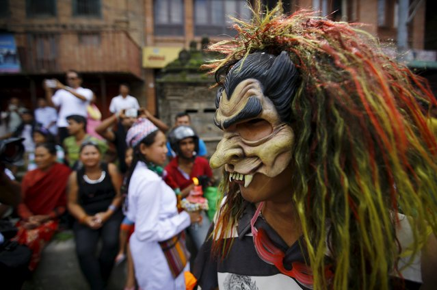 A masked devotee takes part in a parade commemorating the Neku Jatra-Mataya festival, the Festival of Lights, in Lalitpur, Nepal August 31, 2015. (Photo by Navesh Chitrakar/Reuters)