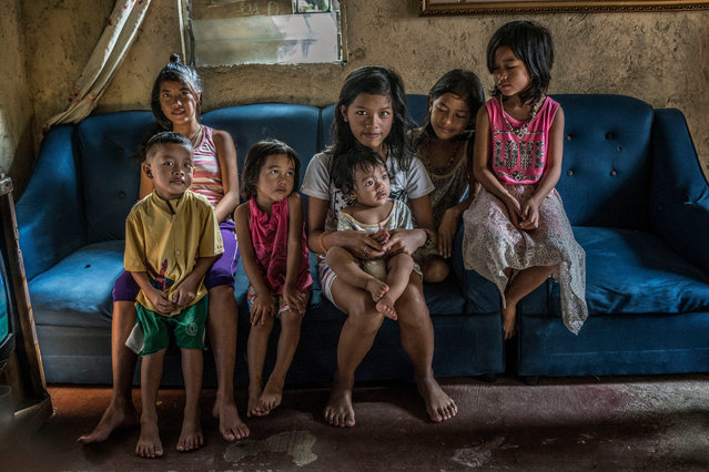 Constantino de Juan's seven children sit on a sofa that still bears the bullet hole from their father's shooting. Juan was preparing a spaghetti dinner on his daughter's birthday when he was killed. (Photo by James Whitlow Delano/Funded by the Pulitzer Center on Crisis Reporting/The Guardian)