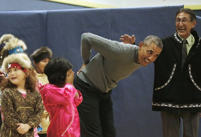 U.S. President Barack Obama jokingly pretends to hurt his back as he dances with children performing a traditional Yup'ik dance at a school in Dillingham, Alaska, September 2, 2015. (Photo by Jonathan Ernst/Reuters)