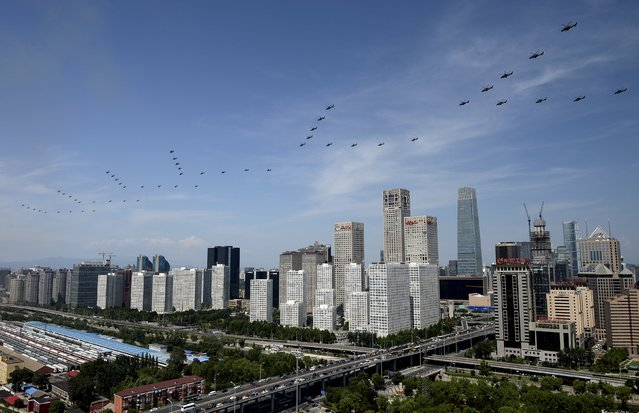 A formation of military helicopters flies past the central business area (CBD) of Beijing, China during the military parade marking the 70th anniversary of the end of World War Two, September 3, 2015. (Photo by Reuters/Stringer)