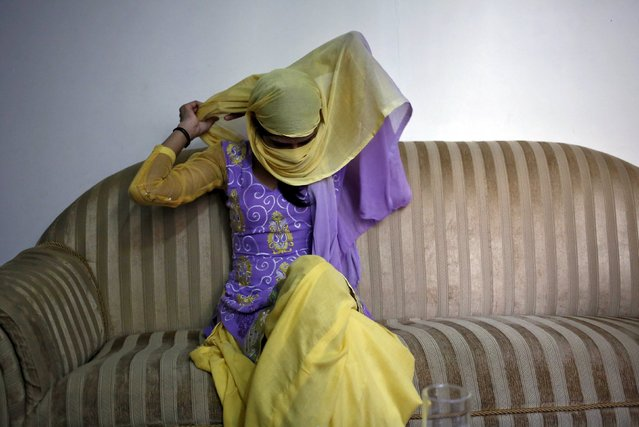 Meenakshi Kumari, 23, one of the two sisters allegedly threatened with rape by a village council in the northern Indian state of Uttar Pradesh, adjusts her headgear as she sits inside her lawyer's chamber in New Delhi, India, September 1, 2015. A village council in northern India has denied allegations that it ordered two young sisters to be raped because their brother eloped with a higher caste woman. (Photo by Anindito Mukherjee/Reuters)