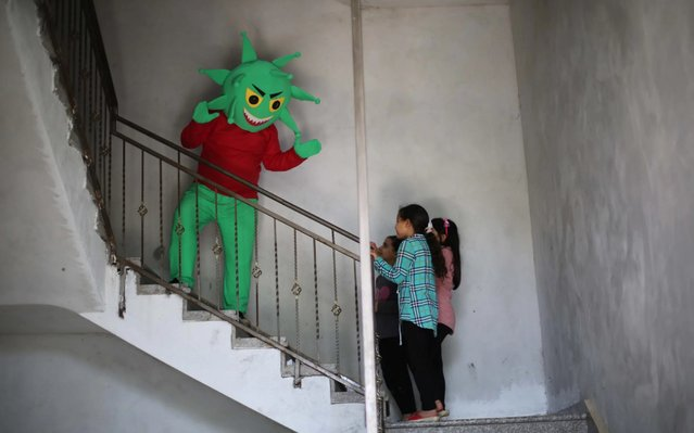 Palestinian Fida El-Ladawi wears a cartoon Covid-19 costume to draw attention of children to the coronavirus (Covid-19) pandemic at Nuseirat Refugee Camp in Gaza City, Gaza on April 19, 2020. (Photo by Hassan Jedi/Anadolu Agency via Getty Images)