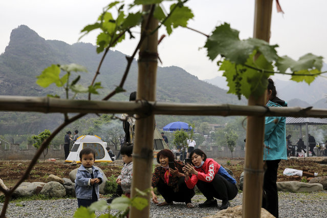 Women take smartphones photos of their children as they gather for a barbecue at a scenic area in Fangshan district in Beijing, Monday, May 4, 2020, after authorities loosened up nationwide restrictions after months of lockdown over the coronavirus outbreak. (Photo by Andy Wong/AP Photo)