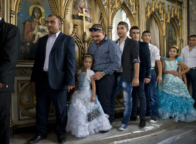 Romanian Roma people pass by icons during a religious service celebrating the Birth of the Virgin Mary at the Bistrita Monastery in Costesti, Romania, Monday, September 8, 2014. (Photo by Vadim Ghirda/AP Photo)