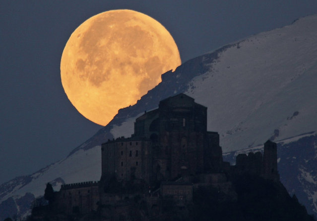 Full Moon setting behind Alps and the Sacra of San Michele: The picture captures the full Moon setting behind the Alps and the Sacra di San Michele, a religious complex situated 1,000 meters up Mount Pirchiriano, some 60 kilometers form Turin, in northern Italy. (Photo by Stefano De Rosa/National Geographic Photo Contest