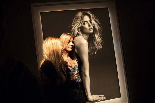 """Martha Hunt, center, stands in front of a photo of herself at a gallery party thrown by Victoria's Secret during New York Fashion Week, September 10, 2014. The gala celebrated photographer Russell James' new book, """"Angels"""". (Photo by Julie Glassberg/The New York Times)"""