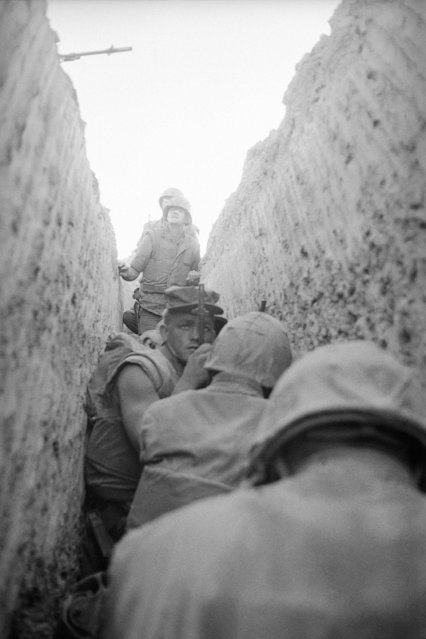 U.S. Marines huddle in trench beside Air Terminal Building at Dong Ha in South Vietnam on September 9, 1967 as the area is shelled by enemy artillery. The Dong Ha combat base is located near the demilitarized zone and receives almost daily swelling and rocket fire from North Vietnamese army positions inside the DMZ. (Photo by AP Photo)