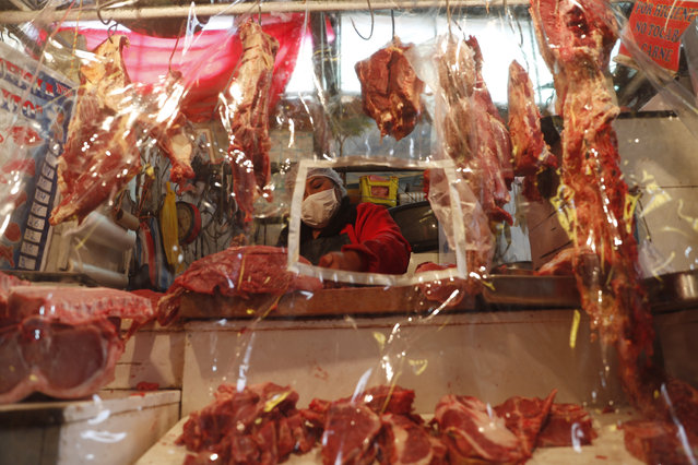 A meat vendor works behind a plastic sheet and wears a face mask as a precaution amid the new coronavirus pandemic at the Villa Fatima market in La Paz, Bolivia, Tuesday, May 19, 2020. The government is limiting residents' movements based on their national ID numbers to essential shopping in the morning, in an attempt to curb the spread of COVID-19. (Photo by Juan Karita/AP Photo)