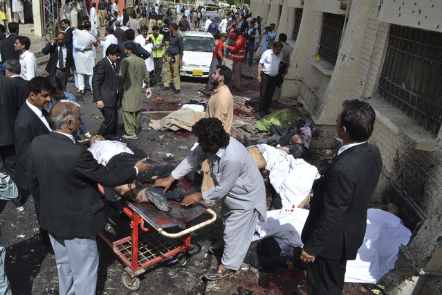 People help victims of a bomb blast in Quetta, Pakistan, Monday, August 8, 2016. A powerful bomb went off on the grounds of a government-run hospital Monday, killing dozens of people, police said. (Photo by Arshad Butt/AP Photo)