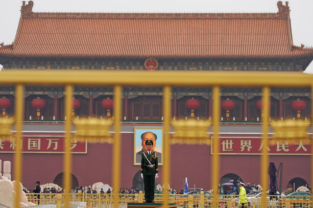 A paramilitary policeman stands guard before a giant portrait of late Chinese Chairman Mao Zedong at the Tiananmen gate, a day before the 19th National Congress of the Communist Party of China begins, in Beijing, China, October 17, 2017. (Photo by Aly Song/Reuters)