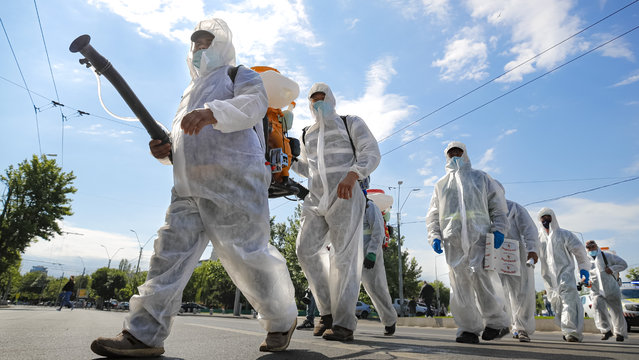 Municipal workers cross a road on their way to disinfect apartment buildings to combat the spread of the coronavirus infection in Bucharest, Romania, Friday, May 22, 2020. Romania loosened a number of lockdown measures imposed two months ago to limit the spread of the COVID-19 infections, but kept social distancing and to wear a face mask while indoors on or public transport. (Photo by Vadim Ghirda/AP Photo)