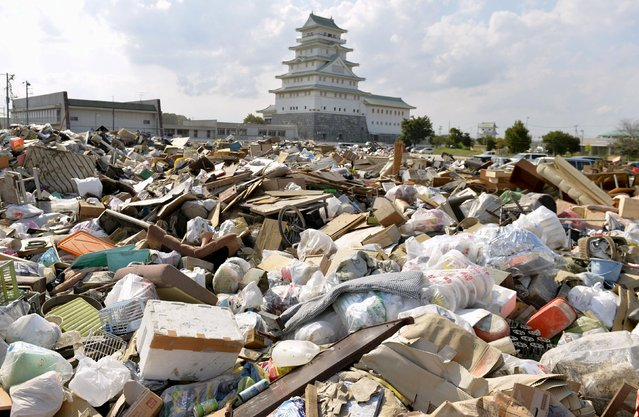 """Household goods damaged by flooding, are piled up at a waste-collection point in front of the castle-shaped Joso City local interchange center known as """"Toyota Castle"""" where hundreds of evacuees from an area flooded by the Kinugawa river, caused by Typhoon Etau in Joso, Ibaraki prefecture, Japan, in this photo taken by Kyodo, September 12, 2015. (Photo by Reuters/Kyodo News)"""
