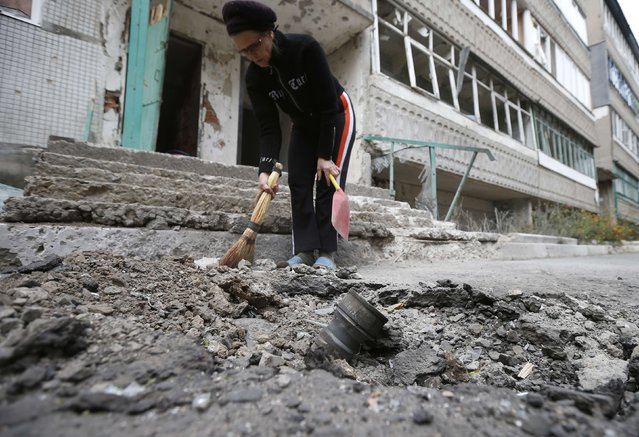 A resident clears debris next to a crater with the remains of a rocket shell after a shelling a day before, in the eastern Ukrainian town of Debaltseve, September 22, 2014. (Photo by David Mdzinarishvili/Reuters)