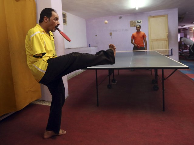 "Disabled table tennis champion Ibrahim Hamato (front), 37, attends a training session at a club in Domiat, northeast of Cairo September 28, 2014. Having lost both his arms in an accident when he was 10, the Egyptian uses his mouth to control his table tennis bat. Living by the motto ""that nothing is impossible as long as you work hard"", Hamato, who has won various tournaments, earned an invitation to the ZEN-NOH 2014 World Team Table Tennis Championships in Tokyo. (Photo by Mohamed Abd El Ghany/Reuters)"