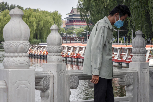 A man wearing a protective face mask to help curb the spread of the coronavirus stands against a roll of boats parked on the barricaded Houhai Lake, a usually popular tourist spot before the new coronavirus outbreak in Beijing, Tuesday, June 30, 2020. China, where the coronavirus pandemic began in December, was the first economy to reopen in March after the ruling Communist Party declared victory over the disease. Manufacturing and other activity is reviving but demand for exports is feeble and Chinese consumers, worried about losing jobs, are reluctant to spend. (Photo by Andy Wong/AP Photo)