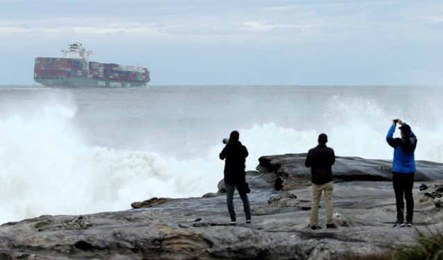 A China Shipping Line container ship sails out from Sydney's Botany Bay port as photographers take pictures of a surfing contest in heavy seas near Australia's largest city, June 6, 2016. (Photo by Jason Reed/Reuters)