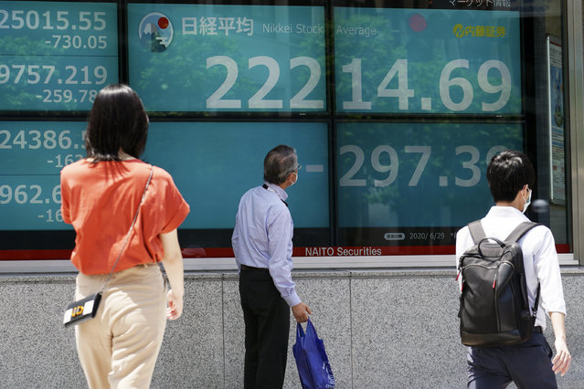 A man looks at an electronic stock board showing Japan's Nikkei 225 index at a securities firm in Tokyo Monday, June 29, 2020. Shares fell Monday in Asia, tracking losses on Wall Street as rising virus cases cause some U.S. states to backtrack on pandemic reopenings. (Photo by Eugene Hoshiko/AP Photo)