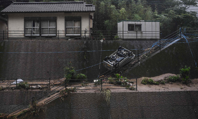"""An overturned car is seen near a residential area hit by torrential rain, in Ashikita, Kumamoto prefecture on July 7, 2020. Emergency services in western Japan were """"racing against time"""" to rescue people stranded by devastating floods and landslides, with at least 50 feared dead and more torrential rain forecast. (Photo by Charly Triballeau/AFP Photo)"""