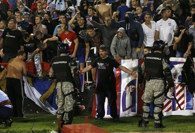Fans of Serbia confront the riot police during the Euro 2016 Group I qualifying soccer match between Serbia and Albania at the FK Partizan stadium in Belgrade October 14, 2014. (Photo by Marko Djurica/Reuters)