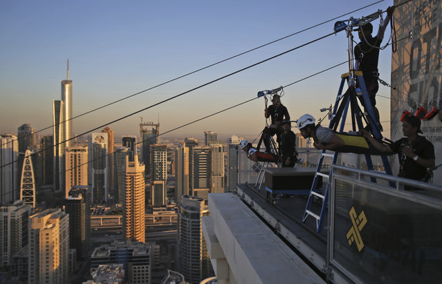 Two people prepare to ride the world's longest urban zip line, with a speed of up to 80 kilometers per hour on a one kilometer run from 170 meter to ground level, in the Marina district of Dubai, United Arab Emirates, Tuesday, December 5, 2017. (Photo by Kamran Jebreili/AP Photo)