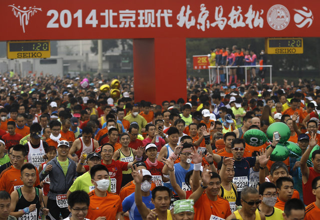 Runners, some wearing masks to protect themselves from pollutants, jog at Tiananmen Square shrouded in haze at the start of 2014 Beijing International Marathon in Beijing, China Sunday, October 19, 2014. (Photo by Andy Wong/AP Photo)