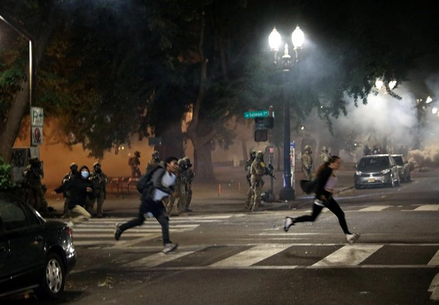 Federal law enforcement officials fire tear gas and other non lethal methods at demonstrators during a protest against racial inequality in Portland, Oregon, U.S., July 19, 2020. (Photo by Caitlin Ochs/Reuters)
