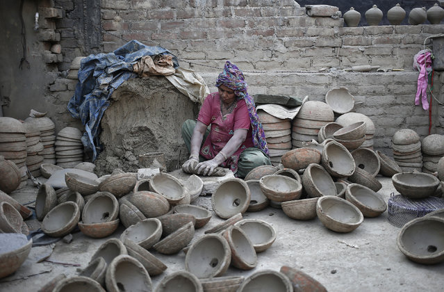 A potter prepares to make earthen pots at a workshop ahead of the Hindu festival of Diwali in New Delhi October 16, 2014. (Photo by Anindito Mukherjee/Reuters)