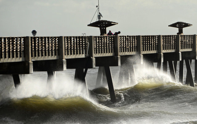 People venture out onto the Jacksonville Beach Fishing Pier as waves crash against the pilings, Friday, September 2, 2016, in Fla. Hurricane Hermine was downgraded to a tropical storm after making landfall on the gulf coast of Florida. (Photo by Bob Mack/The Florida Times-Union via AP Photo)