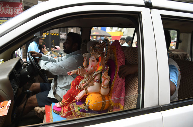 An Indian Hindu devotee transports an idol of the elephant-headed Hindu god, Lord Ganesha in his car, for Ganesh Chaturthi in Mumbai on September 5, 2015. The Ganesh Chaturthi festival, a popular 11-day religious festival which is annually celebrated across India, runs this year from September 5-15, and culminates with the immersion of idols of Ganesh in the Arabian Sea and local water bodies. (Photo by Punit Paranjpe/AFP Photo)