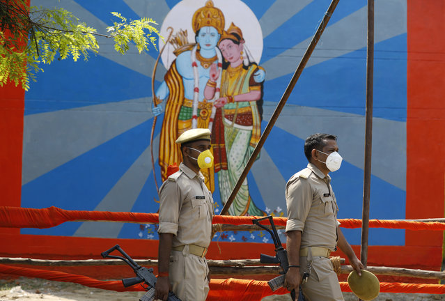 Policemen walk past an image of Hindu god Ram on the eve of a groundbreaking ceremony of a temple dedicated to Ram in Ayodhya, India, Tuesday, August 4, 2020. Wednesday's groundbreaking ceremony follows a ruling by India's Supreme Court last November favoring the building of a Hindu temple on the disputed site in Uttar Pradesh state. Hindus believe their god Ram was born at the site and claim that the Muslim Emperor Babur built a mosque on top of a temple there. The 16th century Babri Masjid mosque was destroyed by Hindu hard-liners in December 1992, sparking massive Hindu-Muslim violence that left some 2,000 people dead. (Photo by Rajesh Kumar Singh/AP Photo)