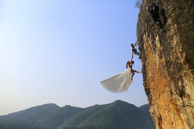 Zheng Feng, an amateur climber takes wedding pictures with his bride on a cliff in Jinhua, Zhejiang province, October 26, 2014. (Photo by Reuters/China Daily)