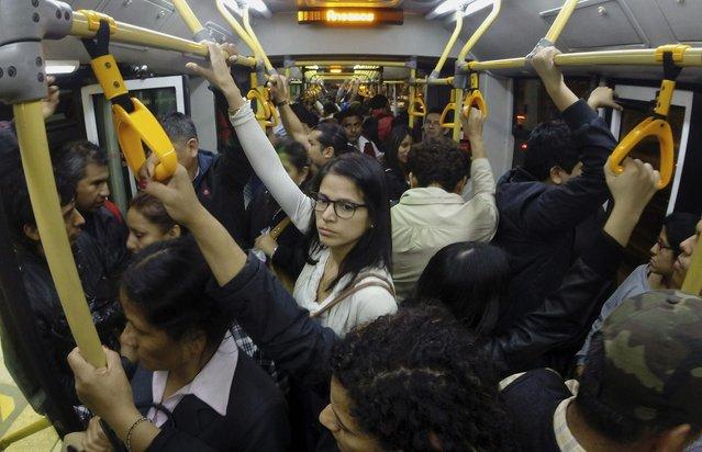 Passengers ride a packed public bus in downtown Lima, October 27, 2014. (Photo by Enrique Castro-Mendivil/Reuters)