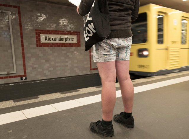 """A participant in the """"No Pants Subway Ride"""" waiting for a train at an underground station in Berlin, Germany, Sunday, January 7, 2018. (Photo by Joerg Carstensen/DPA via AP Photo)"""