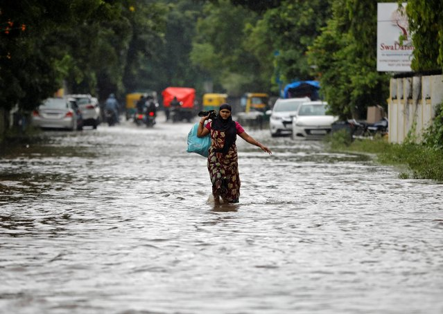 A woman wades through a water-logged road during rains in Ahmedabad, India, August 21, 2020. (Photo by Amit Dave/Reuters)
