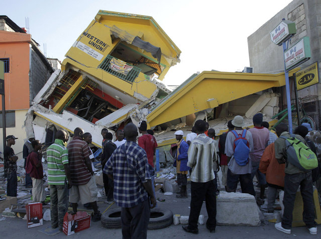 People look at a destroyed building in Port-au-Prince, Haiti, January 14, 2010. (Photo by Jorge Silva/Reuters)