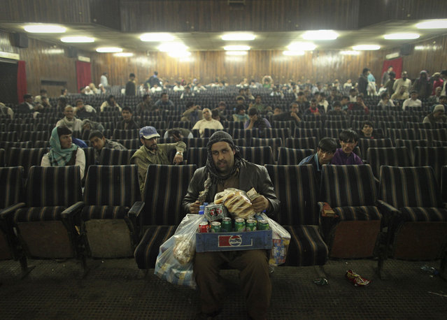 """""""An employee of Cinema Pamir sells refreshments during the movie intermission in Kabul, Afghanistan, on May 3, 2012. Once a treasured luxury for the elite, Afghan cinemas are dilapidated and reflect an industry on the brink of collapse from conflict and financial neglect. Kabul's cinemas show Pakistani films in Pashto, American action films and Bollywood to rowdy, largely unemployed crowds in pursuit of any distraction from their drab surroundings"""". (Photo and comment by Danish Siddiqui/Reuters, India/2013 Sony World Photography Awards"""