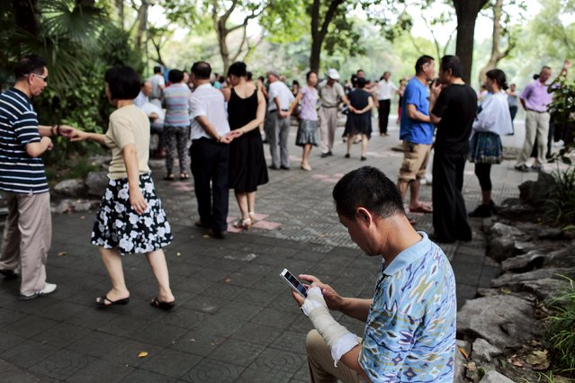 Gao Haibao (C), checks stock information on his mobile phone as he takes a break from dancing, part of his daily routine, at a park near his home in Shanghai, China, July 23, 2015. Gao Haibao, a 55-year-old electrician, started trading stock in the 1990s, he uses smartphones and computers to trade stocks from home. (Photo by Aly Song/Reuters)