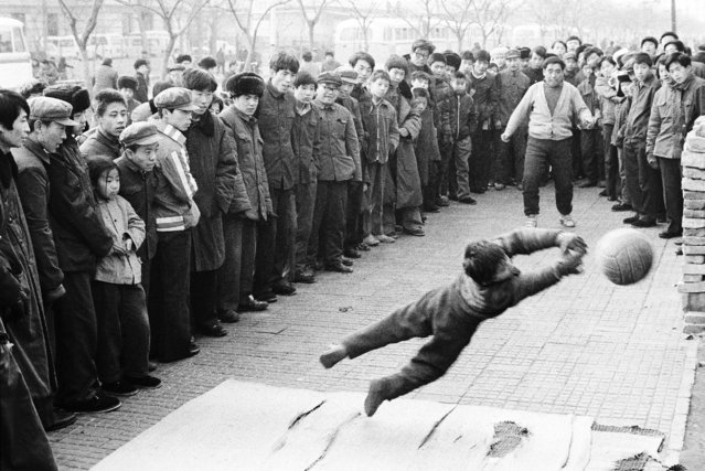 A boy and his father display their soccer skills on a roadside in Beijing in 1981. (Photo by Reuters/China Daily)
