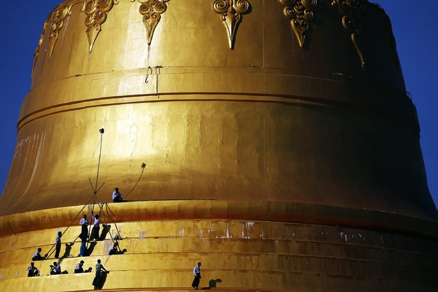 """People work on the golden dome of Uppatasanti Pagoda in Naypyitaw November 10, 2014. Uppatasanti Pagoda, a replica 30cm (12 inches) shorter than the famous Shwedagon Pagoda of Yangon, was inaugurated in 2009 in Myanmar's new capital Naypyitaw. Yangon lost its status as Myanmar's capital in 2005, after the former military junta carved a new seat of government from a parched wilderness some 380 km (236 miles) to the north and called it Naypyitaw (""""Abode of Kings""""). (Photo by Damir Sagolj/Reuters)"""