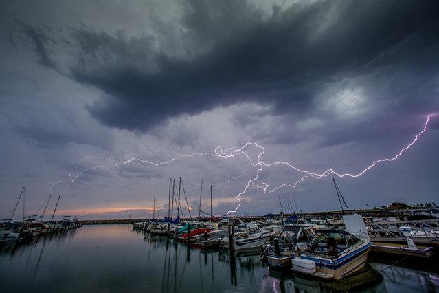 Lightning streaks across the sky over the marina Thursday, July, 21, 2006 in Port Washington, Wi. (Photo by Jeffrey Phelps/AP Photo)