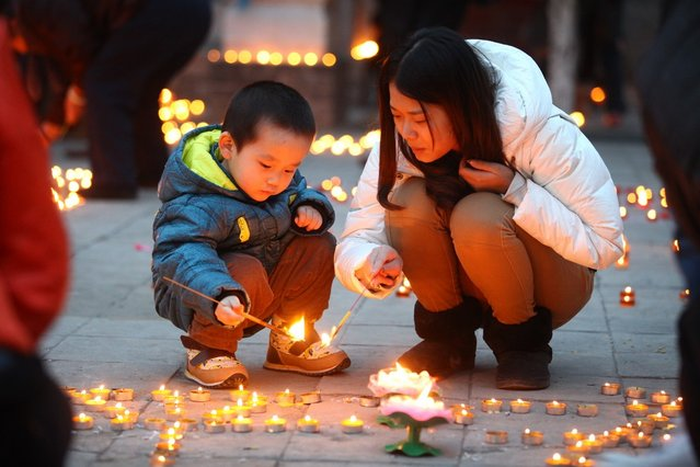 People light candles at Guangren Temple on February 17, 2013 in Xi an, China. The Chinese Lunar New Year of Snake also known as the Spring Festival, which is based on the Lunisolar Chinese calendar, is celebrated from the first day of the first month of the lunar year and ends with Lantern Festival on the Fifteenth day.  (Photo by China Foto Press)